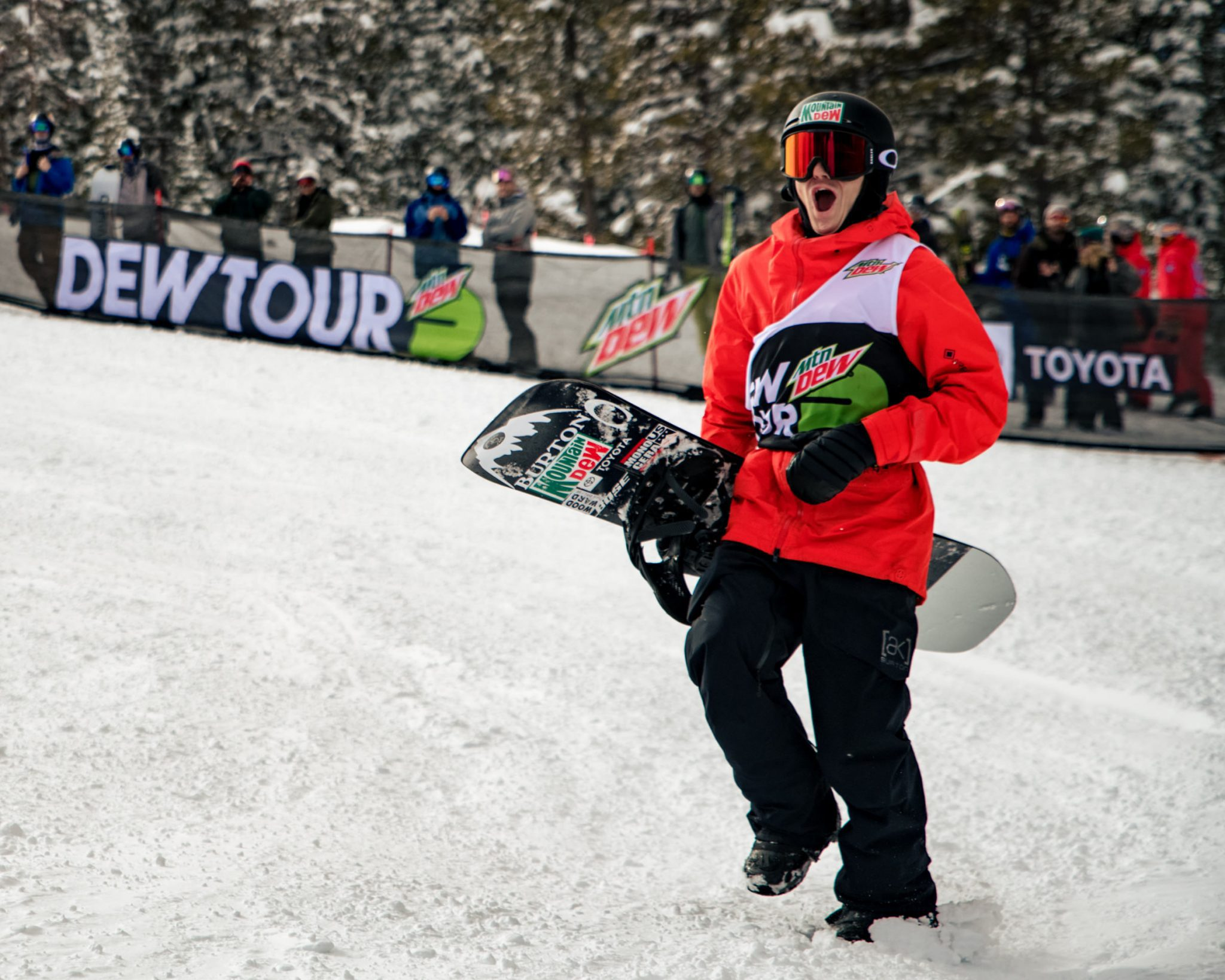 Man at snowboarding competition holding his snowboard after a run