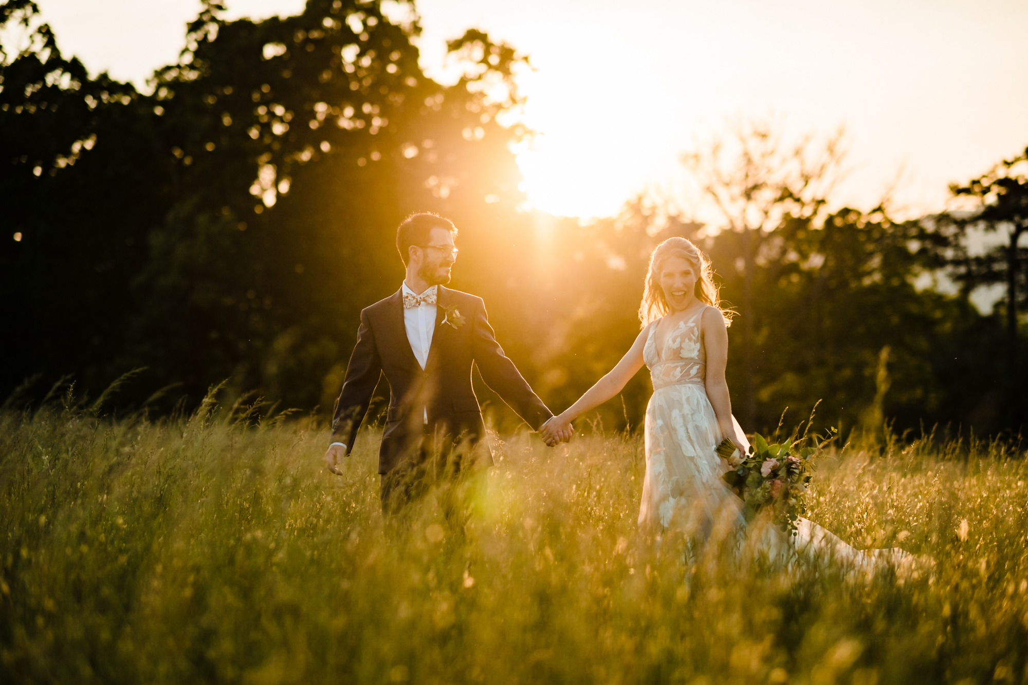bride and groom walking through field at sunset asheville wedding photographer