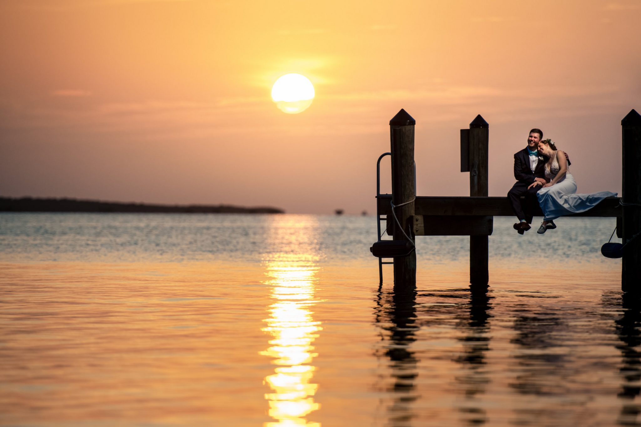 wedding couple sitting on dock at sunset playa largo resort wedding