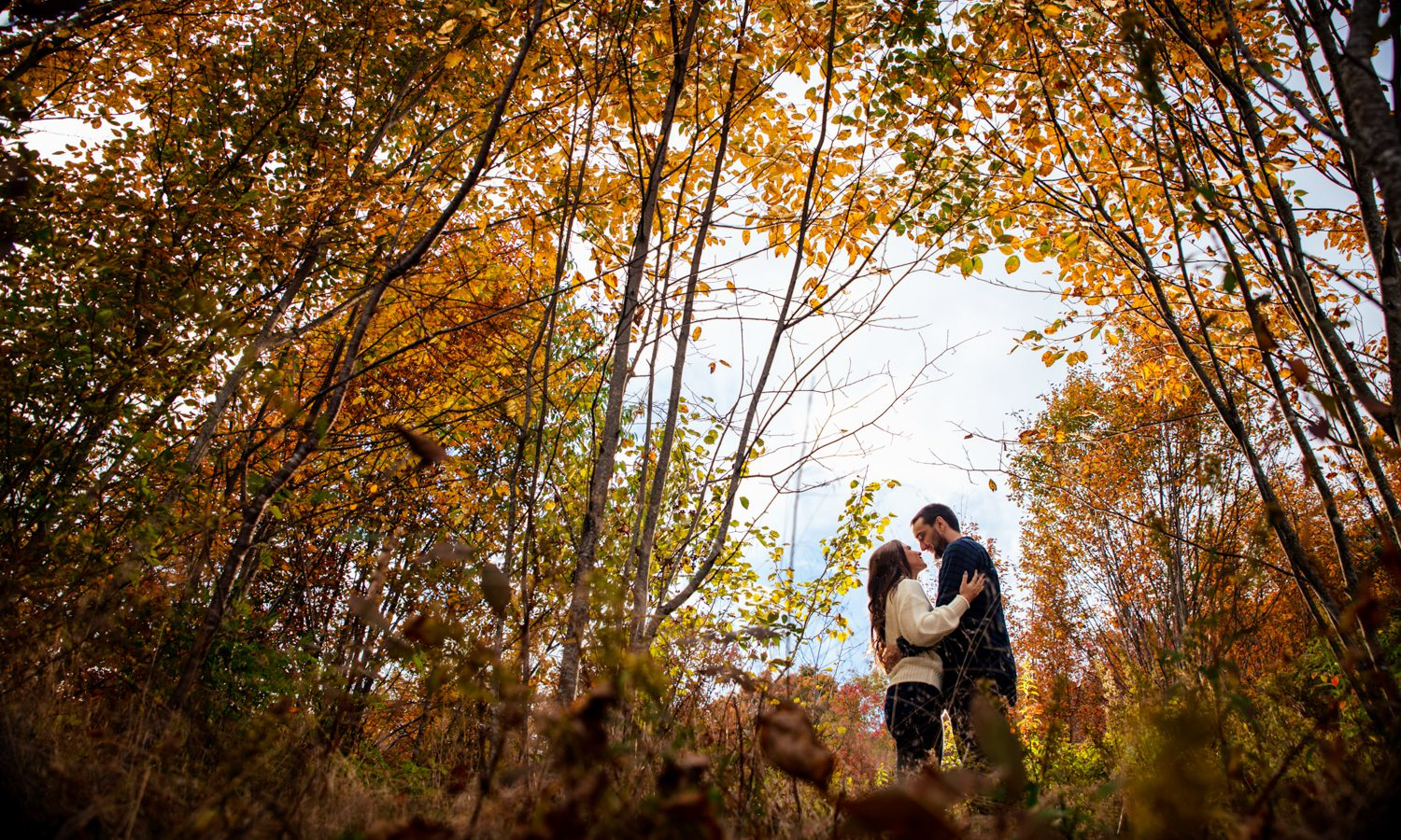couple walking in fall colors at graveyard fields during asheville engagement session
