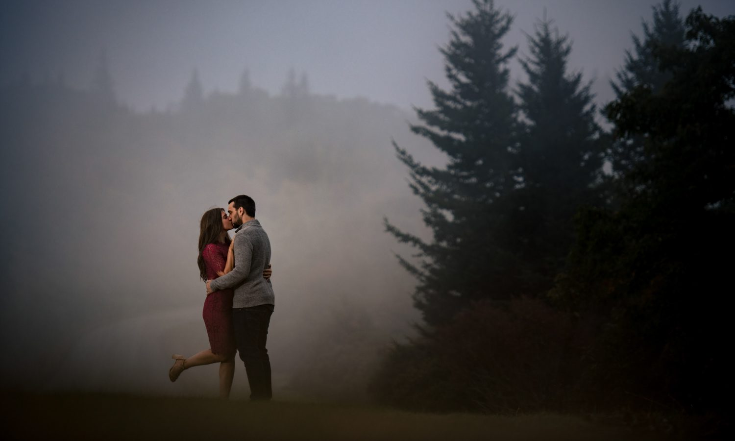 couple in fog on the blue ridge parkway during asheville engagement session