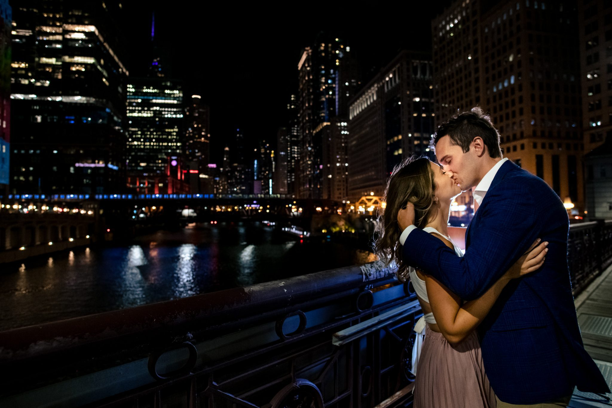 couple kissing on Lasalle street bridge at night during Chicago engagement session